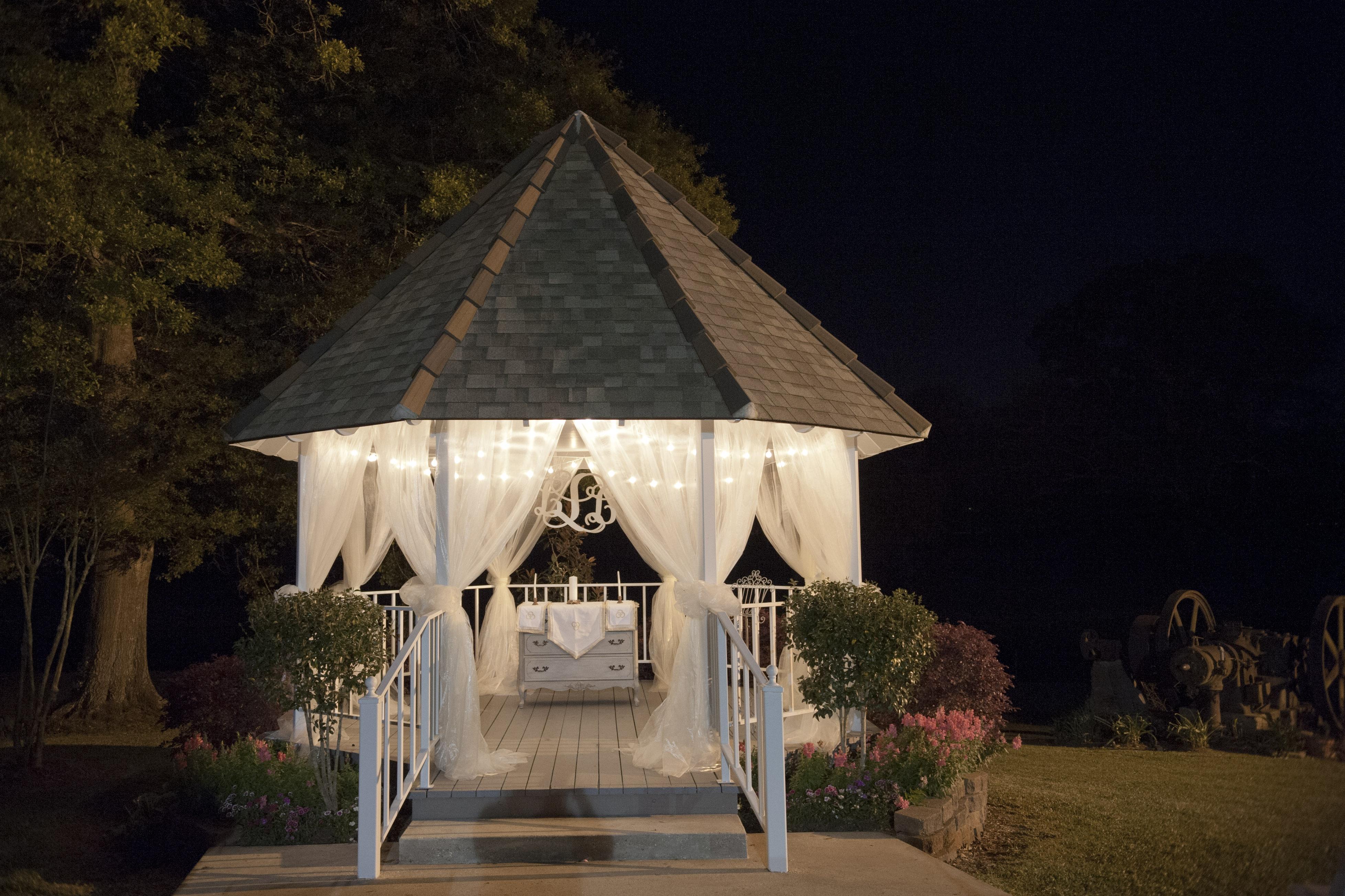 A white outdoor wedding gazebo decorated for a wedding at Poche Bridge Country Club in Breaux Bridge, Louisiana.