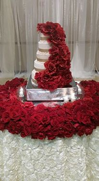 A beautiful wedding cake with red flowers by Miss Jo Cakelady located in Lafayette, Louisiana.