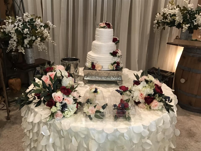 A wedding cake table setup with flowers by Lafayette, Louisiana florist, Poises by Paulie.