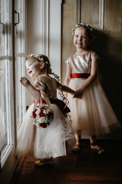 Two cute junior bridesmaids holding hands in the wedding venue, Maison de Tours, located in St. Martinville, near Lafayette, Louisiana.