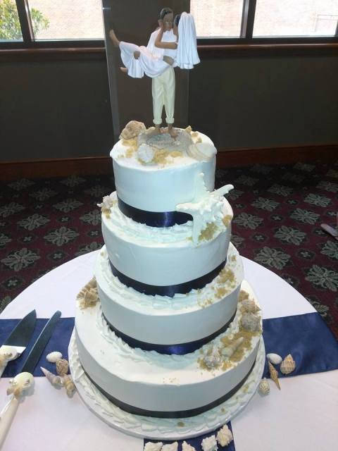 A white and blue wedding cake with a bride and groom on top make by wedding cake baker, Miss Jo Cakelady, located in Lafayette, Louisiana.