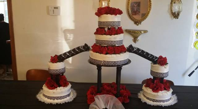 A beautiful wedding cake in white and red with bridges connection tiers by wedding cake baker, Miss Jo Cakelady, located near Lafayette, Louisiana.
