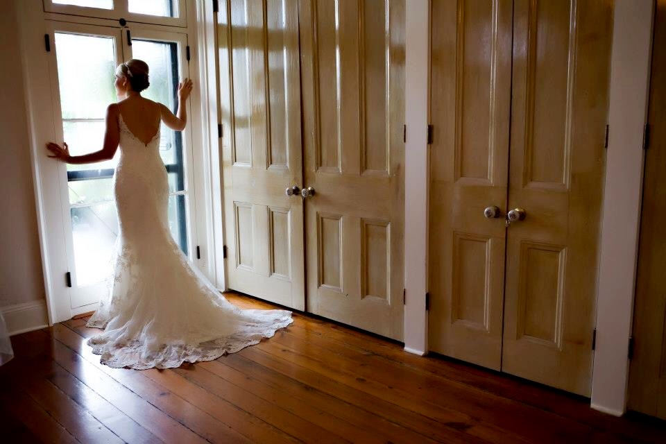 A beautiful bride in front of a full lenght window at the wedding venue, Maison de Tours, located in St. Martinville near Lafayette, Louisiana.