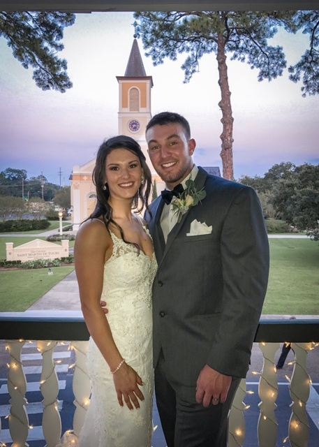 A bride and groom on the upstairs deck at Louisiana wedding venue, Maison de Tours, located near Lafayette, La, with the church in the background.