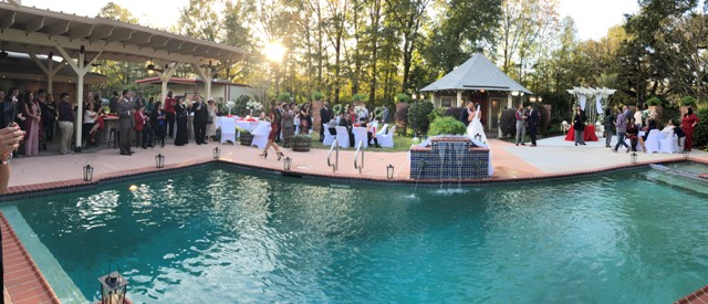 A beautiful, unique photo of the wedding venue located in Lafayette, Louisiana Cajun Mansions, showing an outdoor wedding reception near the pool.