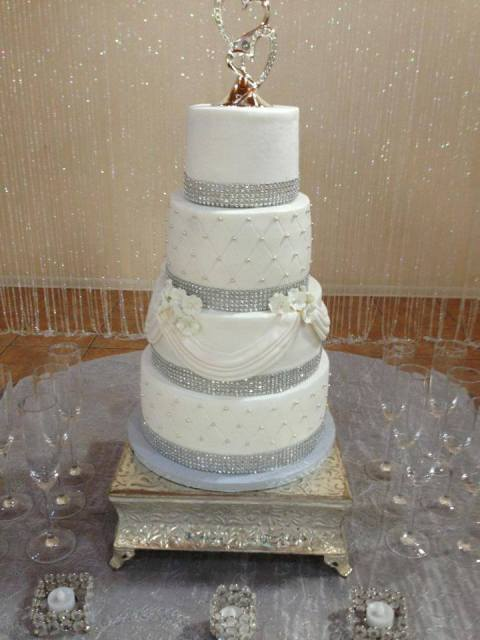 An elegant white and silver wedding cake by Piece of Cake, a bakery located in Lafayette, LA.