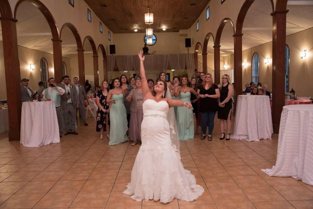 A bride throwing her bouquet at her wedding reception at L'Eglise, a wedding venue located near Lafayette, Louisiana.
