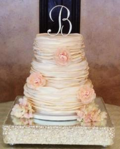 A beautiful white wedding cake with pink flowers and a B on top made by Piece of cake located in Lafayette, Louisiana.