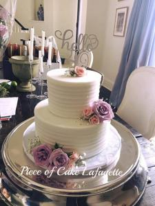 An elegant white wedding cake with lavender and pink flowers made by Piece of Cake, located in Lafayette, LA.