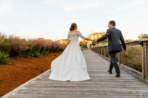 The bride and groom walking on the boardwalk at the wedding venue, The Majestic Hall at Walnut Grove loacted in Lake Charles, Louisiana.