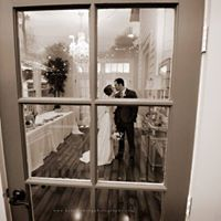 A beautiful bride and groom photo taken through a window after wedding at Esprit de Coeur near Lafayette, Louisiana.