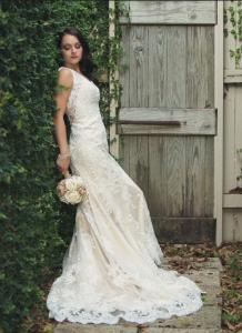 A photo of a beautiful bride taken at the gardens gate at wedding venue, L'Eglise, located near Lafayette, Louisiana.