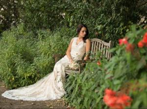 A beautiful bride sitting on a bench in the gardens at L'Glise, a wedding venue located near Lafayette, Louisiana.