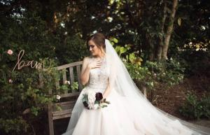 A photo of a beautiful bride sitting on the bench in the gardens at L'Eglise, a wedding venue located near Lafayette, Louisiana.