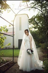 A photo of a beautiful bride taken under the arch in the gardens at L'Eglise, a wedding venue located near Lafayette, Louisiana.