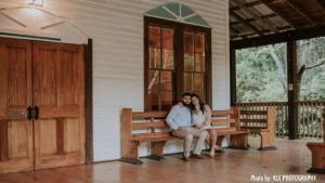 A bride and groom sitting on the bench on the front porch at the wedding venue, Woodlawn Chapel, located in Lafayette, Louisiana.