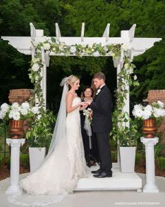 Outdoor wedding with the bride and groom in front of the arch with the minister at the elegant wedding venue Louisiana Cajun Mansion near Lafayette, LA.