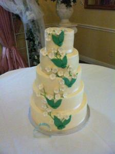 A wedding cake in white and green by Piece of Cake, located in Lafayette, Louisiana.