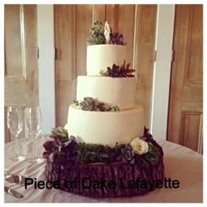 A wedding cake on a wood stand by Piece of Cake, a bakery located in Lafayette, Louisiana.