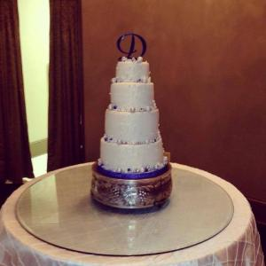 A wedding cake in white with purple trim made by Piece of Cake, located near Lafayette, Louisiana.