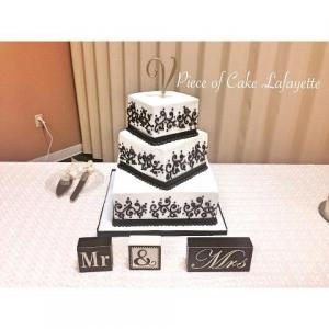A wedding cake in white and black, setup and made by Piece of Cake, a bakery located near Lafayette, Louisiana.