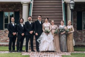 The bride and groom with their wedding party in front of steps by wedding photographer, DK Hebert Photography, located near Lafayette, Louisiana.