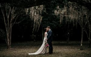 A bride and groom kissing under the oak trees which are hanging with moss by wedding photographer, DK Hebert Photography, near Lafayette, LA.
