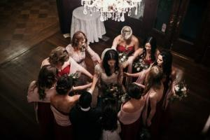 A bride with her wedding party saying a prayer before the ceremony, by wedding photographer, DK Hebert Photography, located near Lafayette, Louisiana.