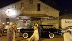 The front view of Louisiana wedding venue, Feed N Seed, located in Lafayette, Louisiana with the bride and groom in front of an antique car.