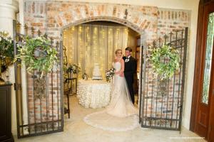 A bride and groom near their wedding cake at the elegant wedding venue near Lafayette, Louisiana called Louisiana Cajun Mansions.