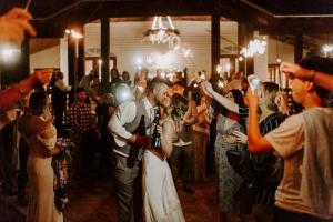 A photo of a bride and groom leaving a reception at the wedding venue, Woodlawn Chapel, located near Lafayette, Louisiana.