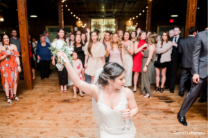 A beautiful bride throwing her bouquet at the wedding venue near Lafayette, Louisiana, Warehouse 535.
